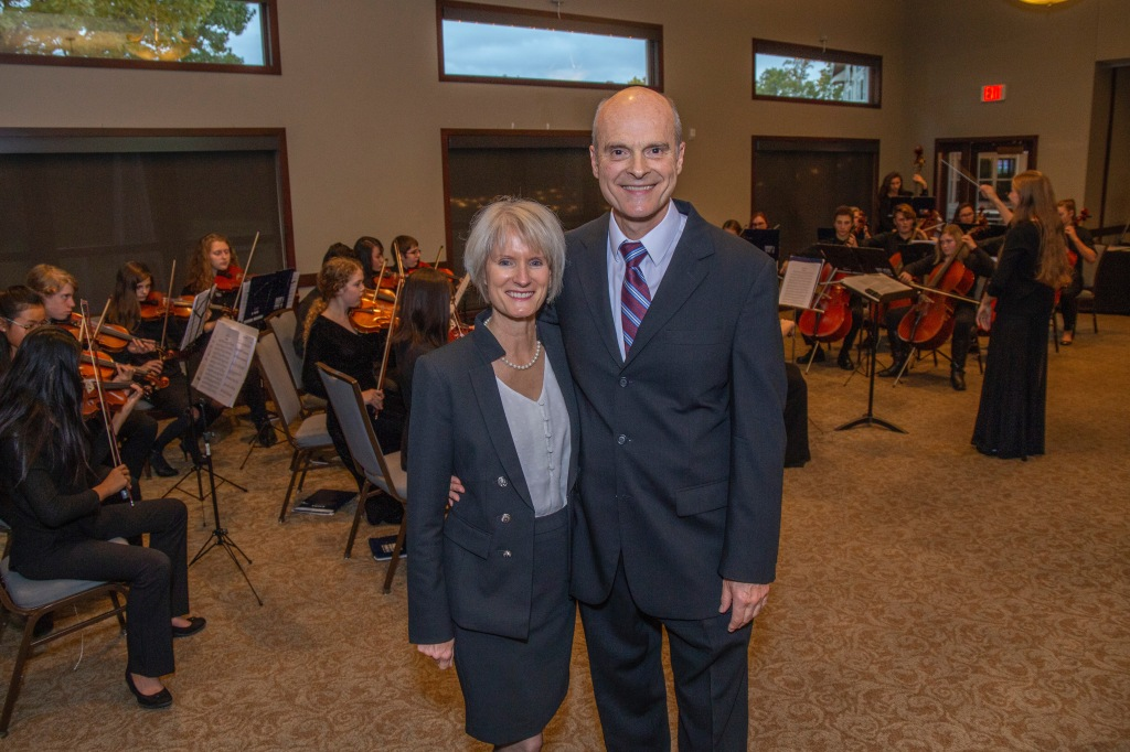 Brian Morris stands with his wife, Debbie, in front of a string ensemble that is performing.
