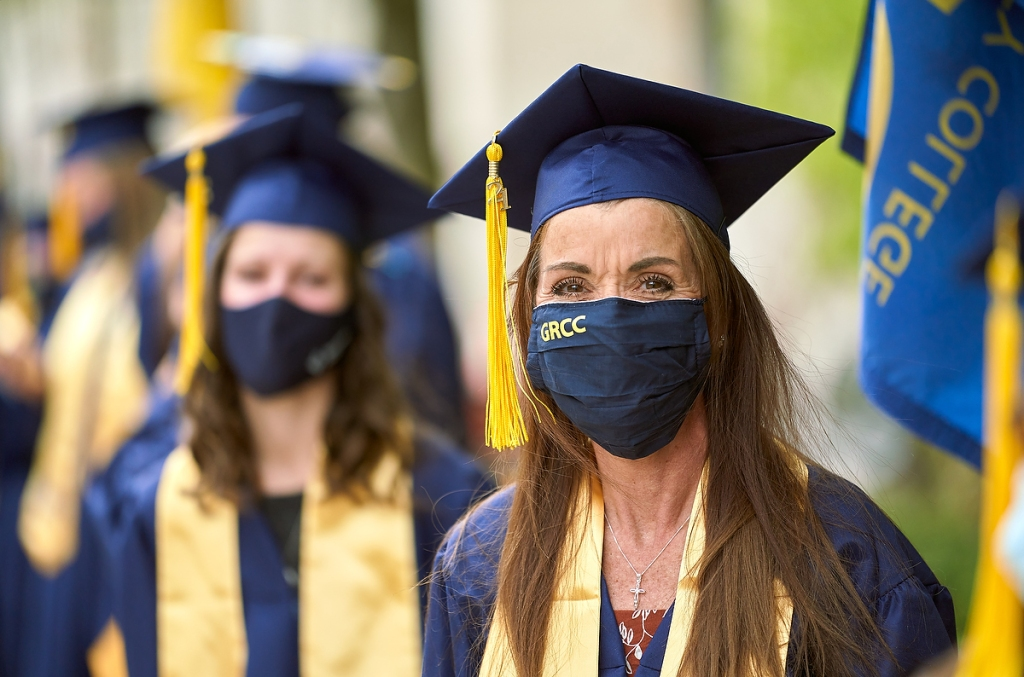 Amy Maggini wears a facemask along with her commencement gown, stole and mortarboard.