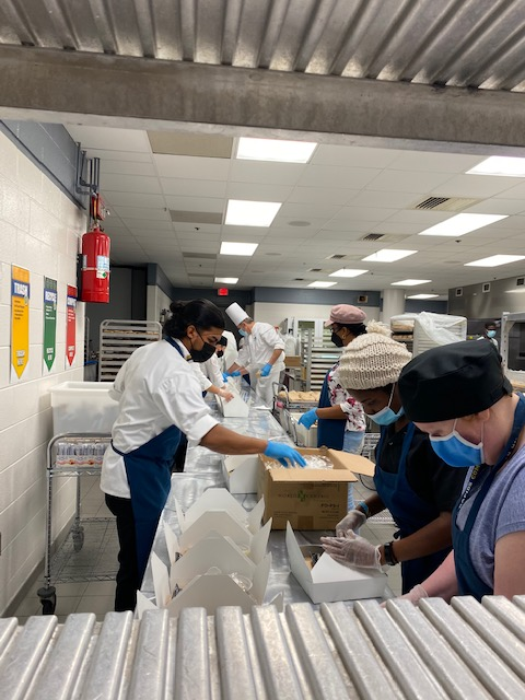 Culinary students work on boxed lunches.