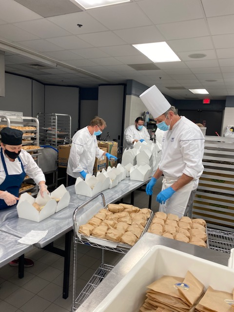 Culinary instructors and students work on boxed lunches.