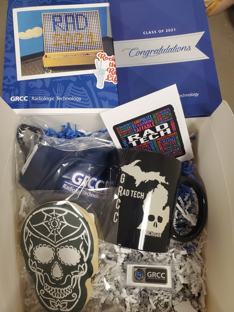 A gift box contains a mug, cookie, pin and facemask.