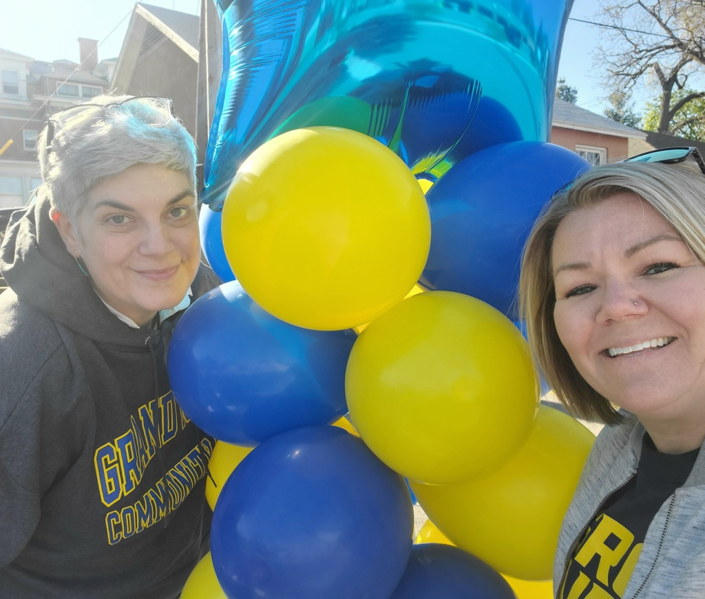 Heather Klare and Julie Lacksheide stand next to a balloon tower.