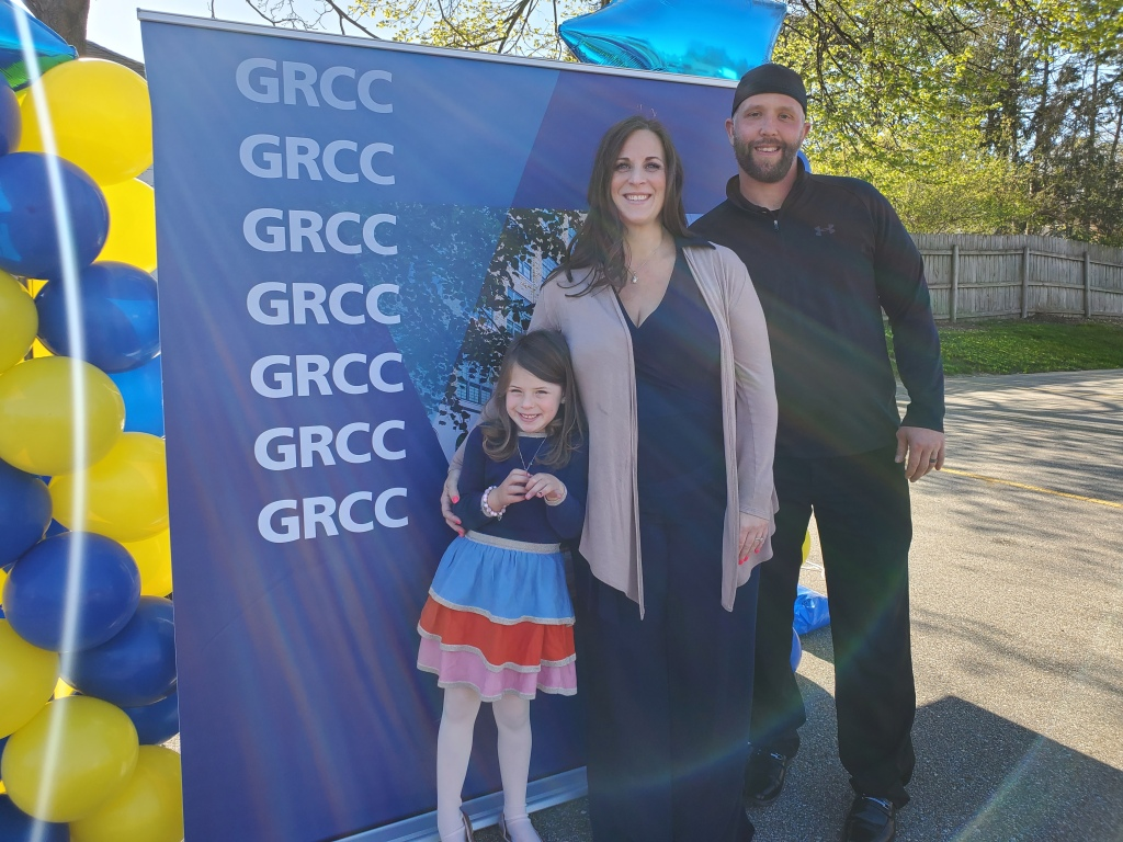 A man, woman and little girl stand in front of a GRCC backdrop.