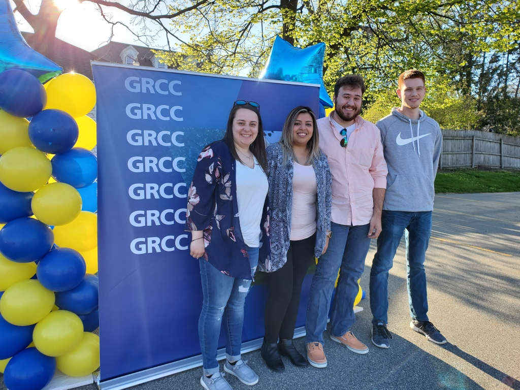 Four students stand in front of a GRCC backdrop.