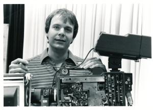 Mark Vogel smiling while holding computer parts.