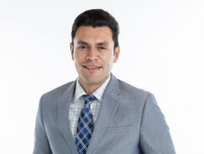 WOOD journalist Ruben Juarez wearing a suit and smiling.