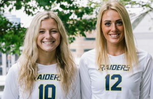 Kylie Oberlin and Annie Holesinger wearing volleyball uniforms and smiling.